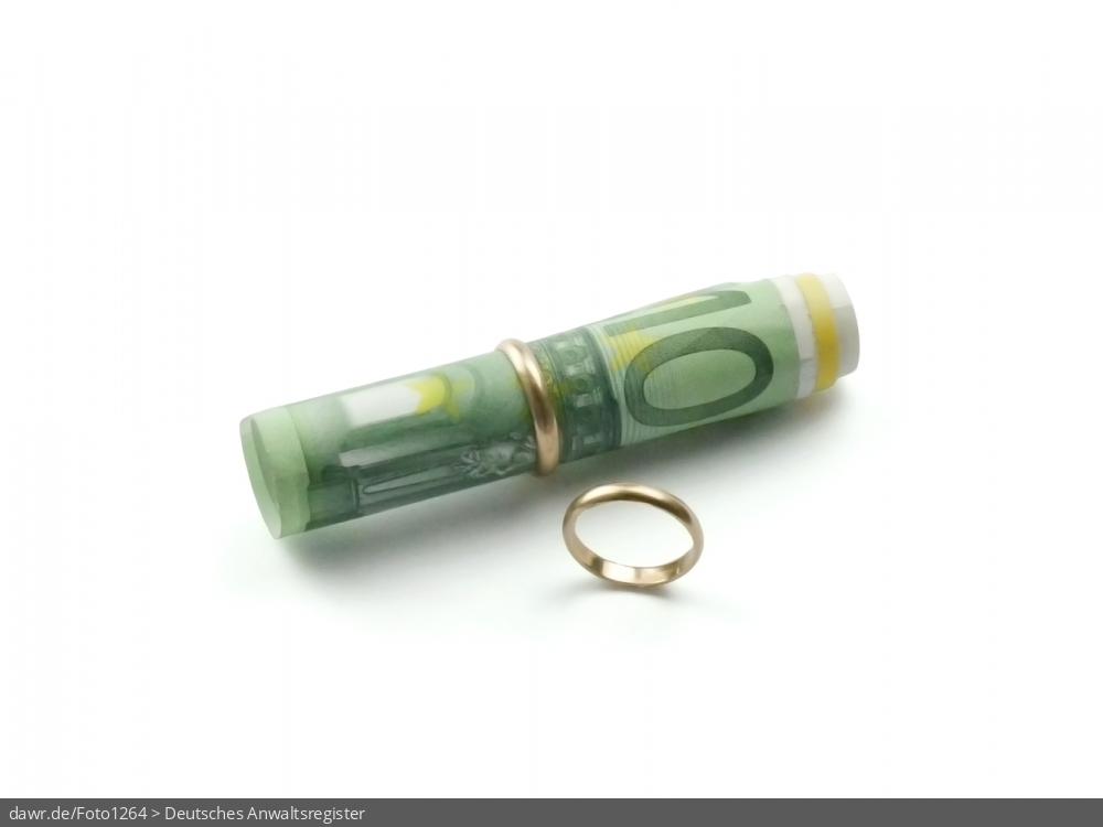 Dieses Foto zeigt eine Rolle aus 100Euro Banknoten, auf die ein Ehering steckt wurde. Ein zweiter Ehering steht deutlich abseits vom ersten vor der Geldrolle. Dieses Bild eignet sich gut als symbolische Darstellung für das Thema Scheidungskosten oder allgemein Geld und Scheidung.