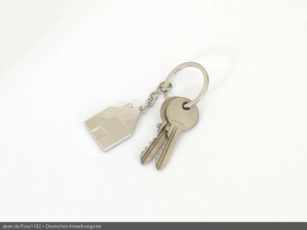 Dieses Foto zeigt einen kleinen Schlüsselbund mit zwei Schlüsseln und einem Schlüsselanhänger in der Form eines Hauses.